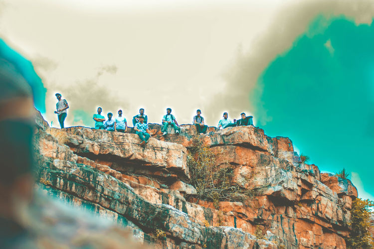 People on rock formation against sky
