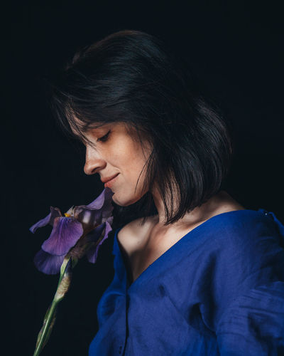 Close-up of woman holding purple flower against black background