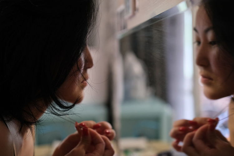 Close-up of woman with black hair looking in mirror at home