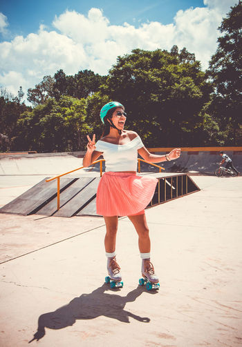 Cheerful woman skating at skateboard park