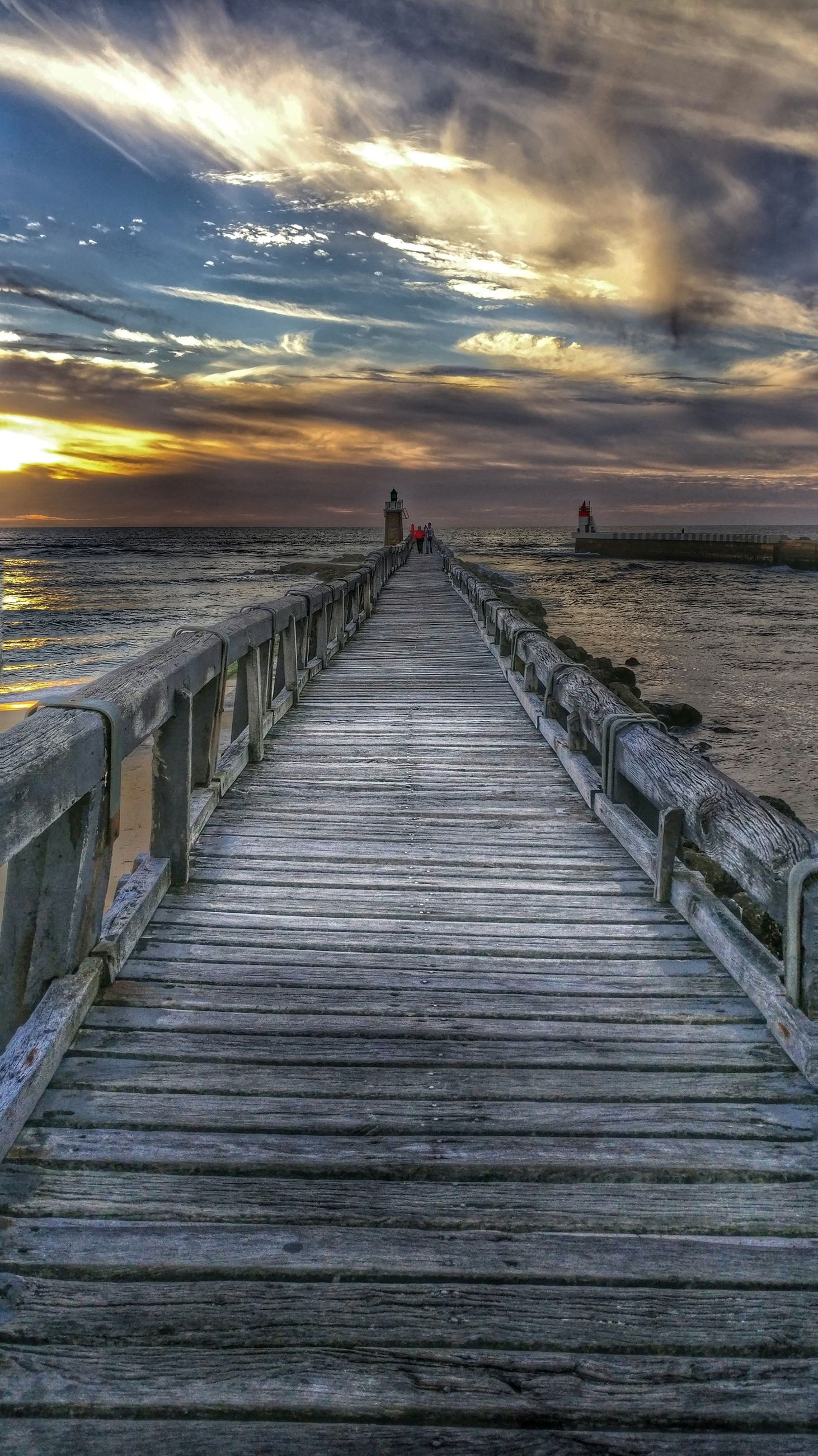 sunset, sea, the way forward, tranquil scene, scenics, tranquility, water, pier, idyllic, sky, cloud, horizon over water, beauty in nature, long, boardwalk, cloud - sky, calm, nature, diminishing perspective, ocean, railing, relaxation, wood paneling, vacations, dramatic sky, narrow, non-urban scene, outdoors, majestic, remote, summer, sunbeam, tourism, sun