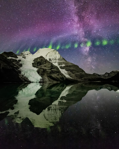 Solar activity has been minimal over the past couple of months so here is a fresh edit from the September last year. This shot is looking South towards the North Face of Mt Robson with the Milky Way rising along with the aurora related phenomena of 'Steve' accompanied by a 'Picket Fence' travelling east west above it. Berg Lake sits at an altitude of 1,646 m (5,400 ft). The North Face of Mt Robson rises 2,308m (7,572ft) out of the lake to a total height of 3,954 m (12,972 ft) and is the highest peak in the Canadian Rockies. Mount Robson Provincial Park, British Columbia, Canada. I had previously edited up some landscape shots of this; however noticed that I also had a few portrait shots to play with. The image has the mountain stacked from multiple frames to reduce noise; yet uses a single image of the sky and water as stacking the sky over multiple frames would remove the definition in the aurora. Love Life, Love Photography Aurora Borealis Berg Lake British Columbia, Canada Steve Astronomy Beauty In Nature Cold Temperature Galaxy Idyllic Lake Milky Way Mountain Nature Night Picket Fence Aurora Reflection Scenics - Nature Sky Snowcapped Mountain Space Star - Space Tranquil Scene Tranquility Water Waterfront