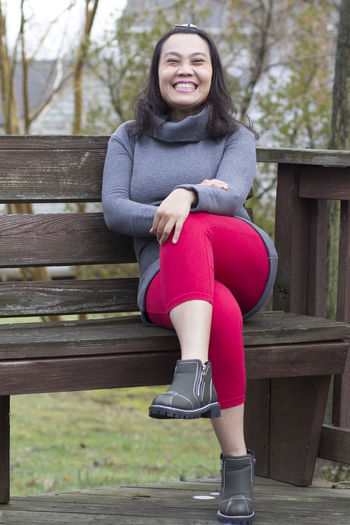 Portrait of smiling mature woman sitting on bench in park