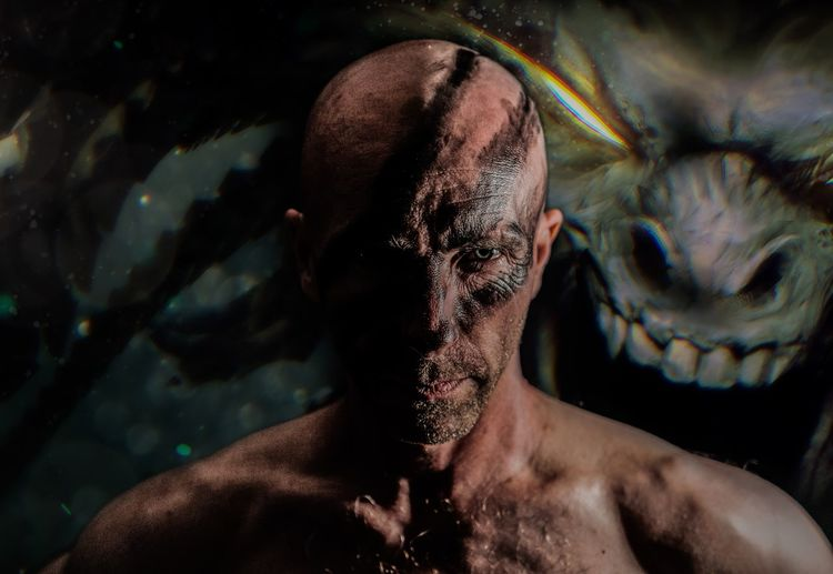 Portrait of bald man with face paint against spooky background