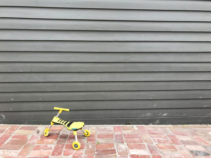 Backyard Brick Day Grey Grey Wall Kids Toy Kids Toys Kids Tricycle Lines Lines And Shapes Outdoors Suburban Suburban Landscape Toy Tricycle Tricycle Yellow Yellow Tricycle