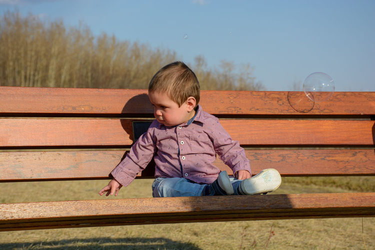 Baby sitting on a bench at the park