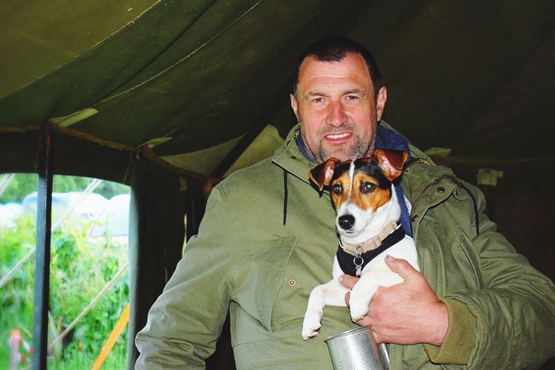 Portrait of smiling man with jack russell terrier standing in tent at campsite