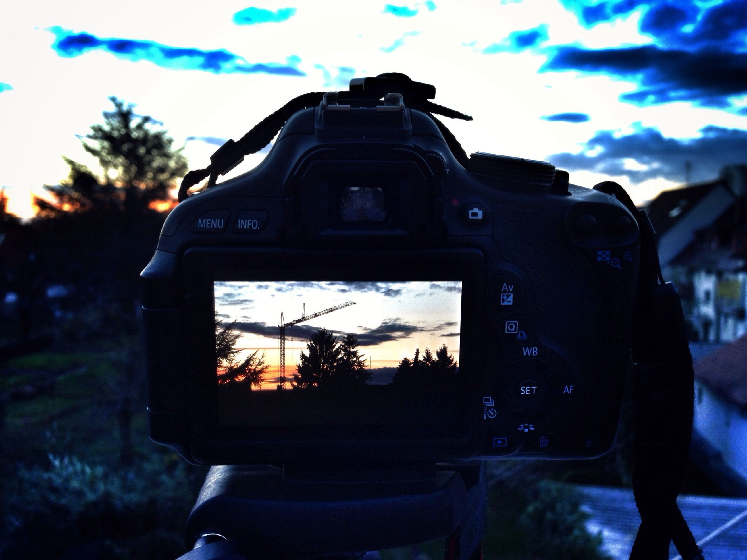 sky, sunset, tree, silhouette, cloud - sky, cloud, dusk, focus on foreground, technology, outdoors, low angle view, land vehicle, building exterior, close-up, nature, built structure, one person, sunlight, photography themes