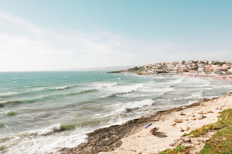 Beach Beach Umbrella Beauty In Nature Distant View Grass Horizon Horizon Over Water Loneliness Nature Outdoors Real People Rocky Beach Sand Scenics Seashore Shore Sicily Sky Tranquil Scene Tranquility Tranquility Umbrella Waves, Ocean, Nature Windy Day