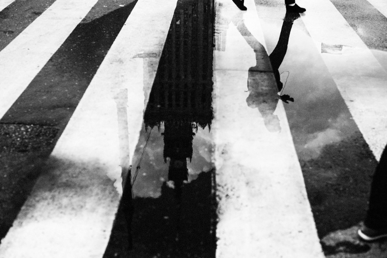 Low section of man reflecting on water at zebra crossing