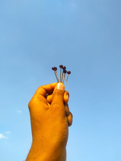 Cropped image of man holding needles against blue sky