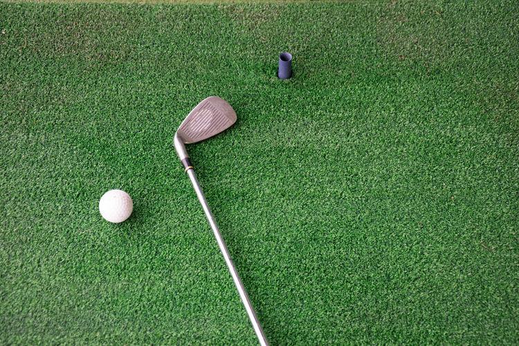 High angle view of golf ball and iron on driving range