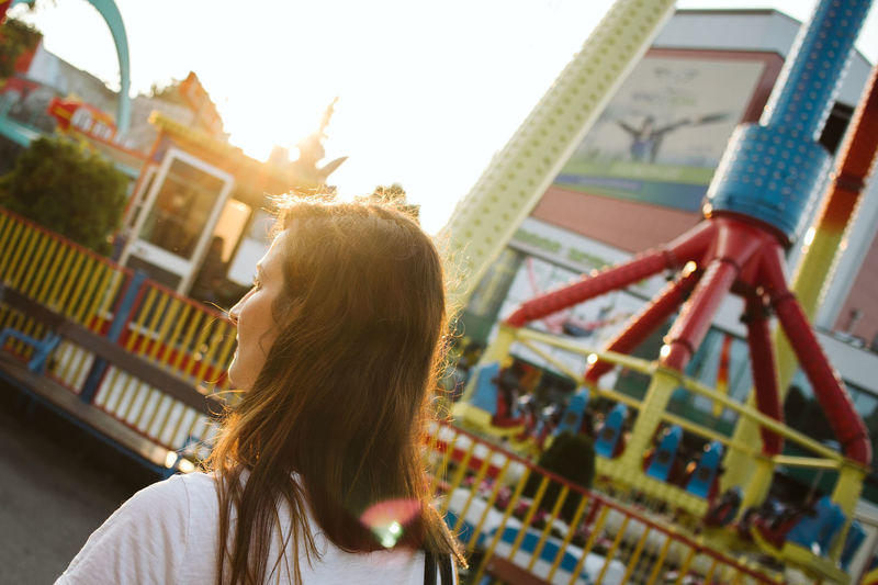 Rear view of woman standing at amusement park during sunset