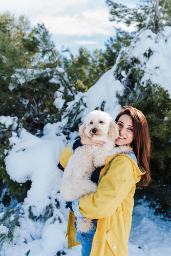 Portrait of smiling woman with dog in snow