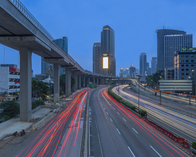 Light trails on road amidst buildings in city against sky