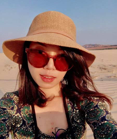 Portrait of beautiful young woman wearing hat at beach