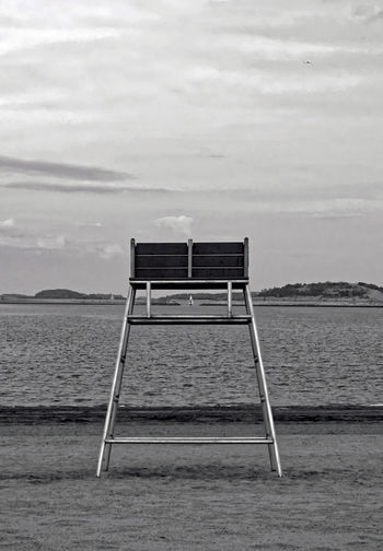 Black and white image of an empty lifeguard chair fronting a Castle Island beach in Boston, Massachusetts. Alone Beach Beauty In Nature Black And White Boston Castle Island Day Greyscale Landscape Lifeguard Chair Monochrome Nature No People Non-urban Scene Outdoors Remote Scenics Sea Seascape Sky Solitude Tranquil Scene Tranquility Water Waterfront