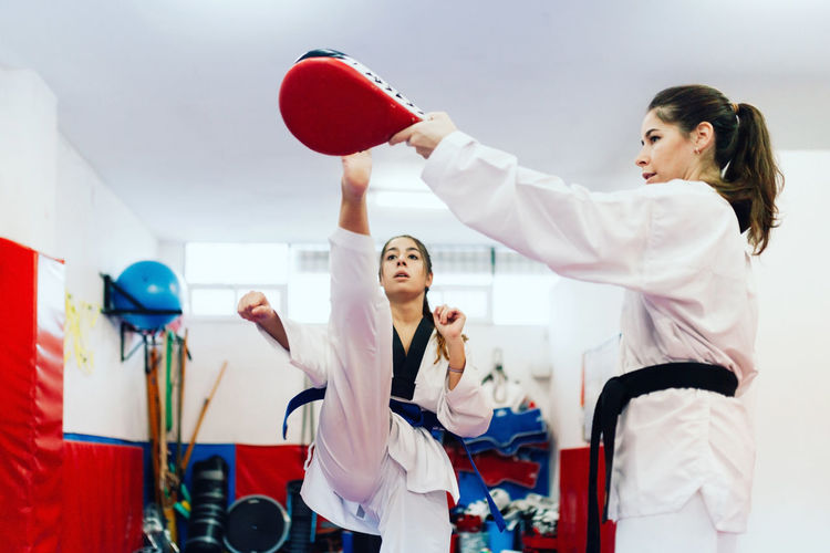 Young woman with instructor practicing martial arts