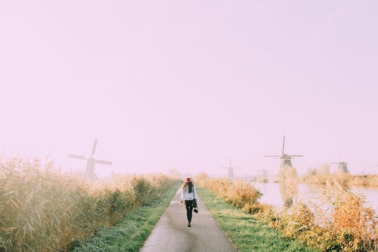 Rear view of woman walking on road in kinderdijk village