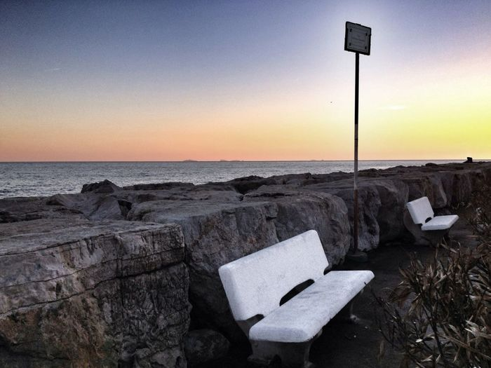 Benches by sea at sunset