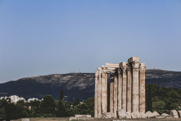 Greek temple ruins on mountain against blue sky