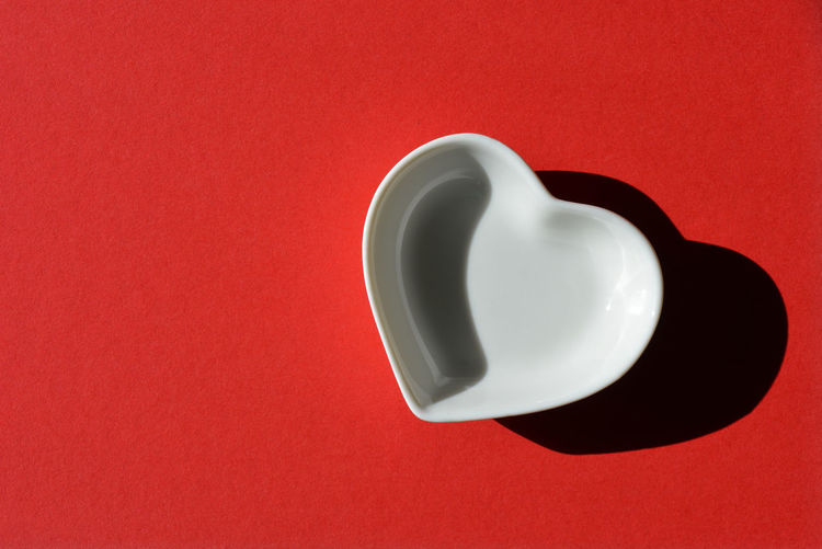 Directly above shot of empty tea cup against red background