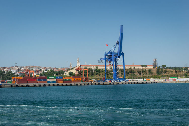 Cranes by sea against clear sky