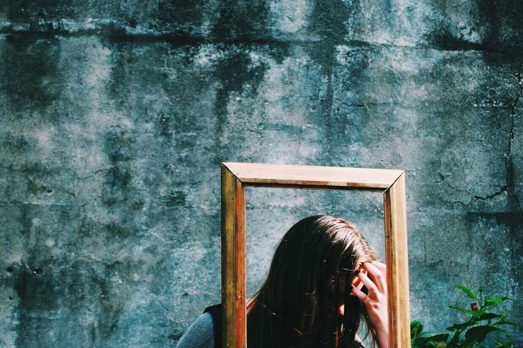 Sad woman by wooden frame against old wall