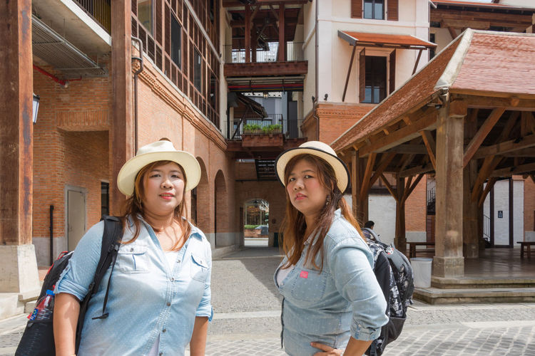 Portrait of twin sisters standing against built structures
