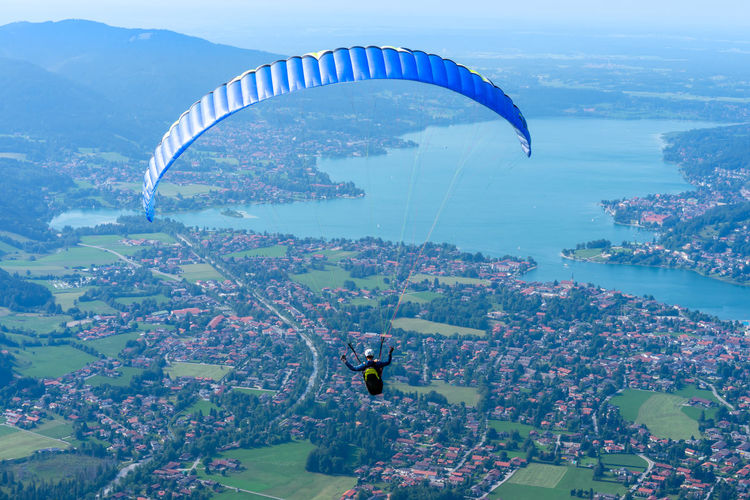 Rear view of man paragliding over townscape
