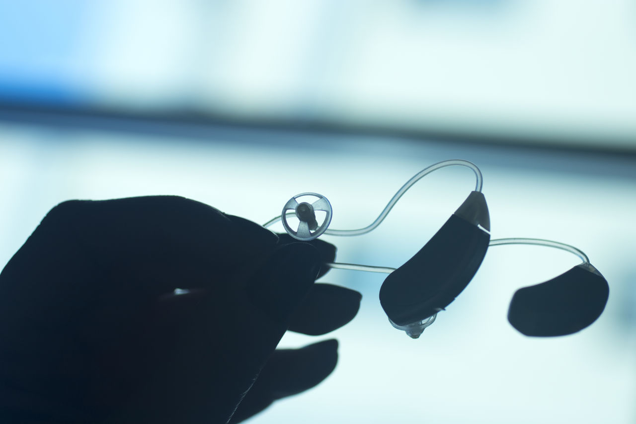 CLOSE-UP OF HAND HOLDING GLASS WITH EYEGLASSES