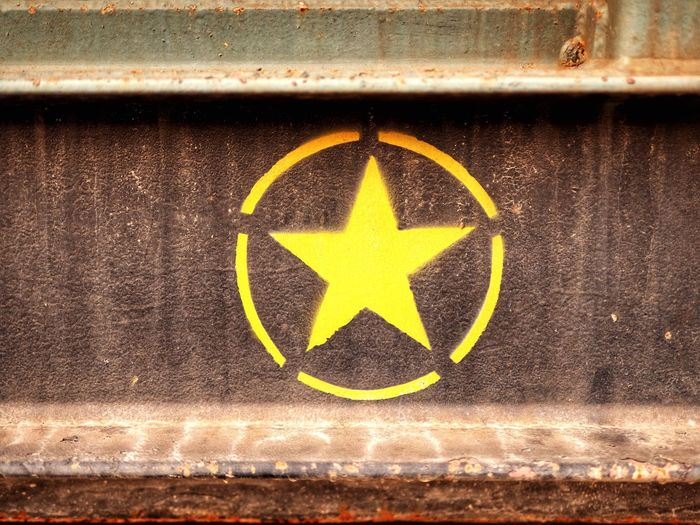Close-up of yellow painted sign on water
