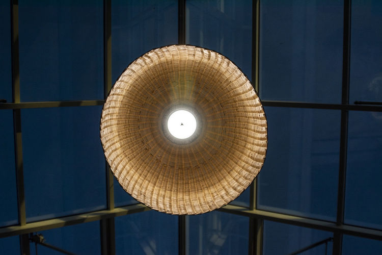 Low angle view of illuminated pendant light hanging on ceiling in building