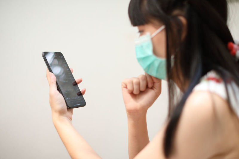 Woman wearing mask using mobile phone at table