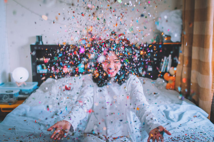 Happy Young Woman Throwing Confetti While Sitting On Bed At Home