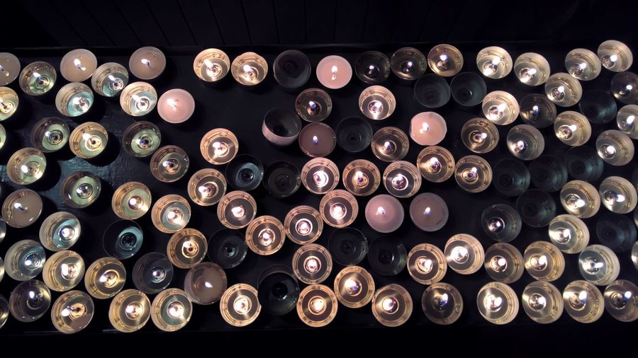 High angle view of lit tea light candles over black background