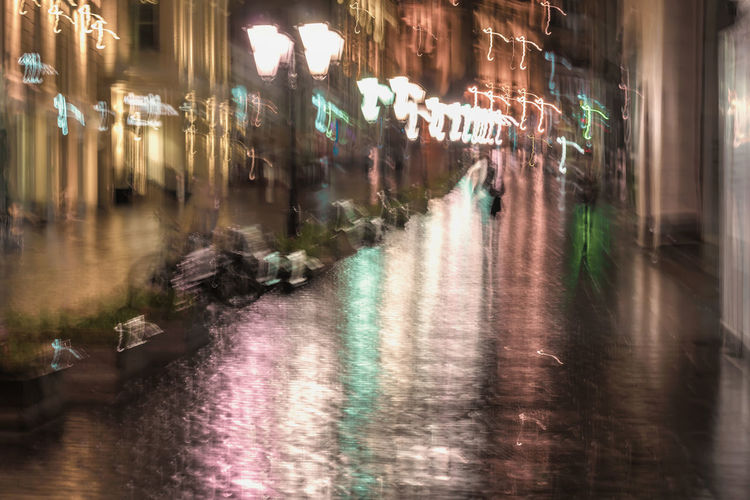 Late evening in the deserted city, lonely pedestrians rush home, rainy late evening. Bright illumination, reflection in wet pavement. Concept of modern city, loneliness and sadness. Abstract blurred background Illuminated City Night Motion City Rainy Rain Blurred Motion Blur Abstract Evening Street Bright People Reflection Lamps Pavement Umbrella Rainy Season Architecture Water Wet Long Exposure Outdoors No People