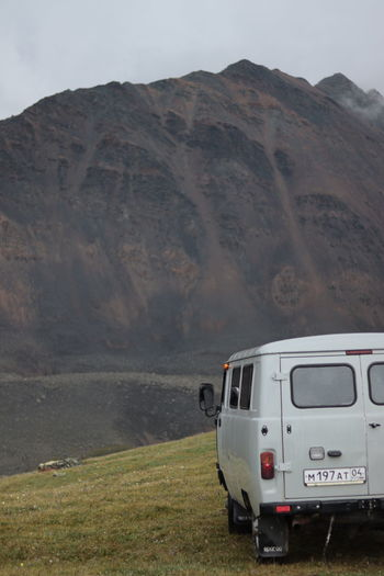 Vintage car on field against mountains