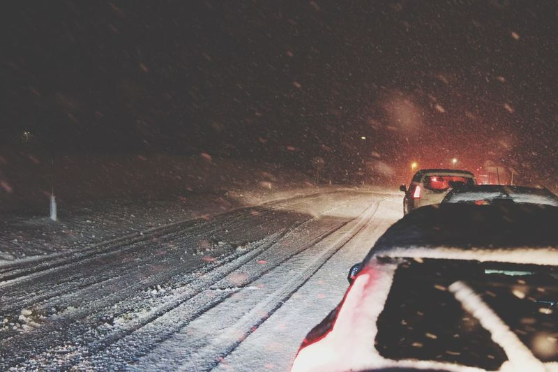 Car on snow covered road against sky at night