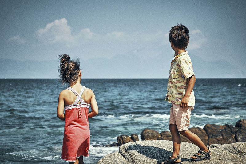 Beach Boy Child Childhood Family Girl Horizon Horizon Over Water Land Leisure Activity Lifestyles Nature Outdoors Real People Rear View Rock - Object Sea Sea And Sky Sky This Is Family Water Visual Creativity