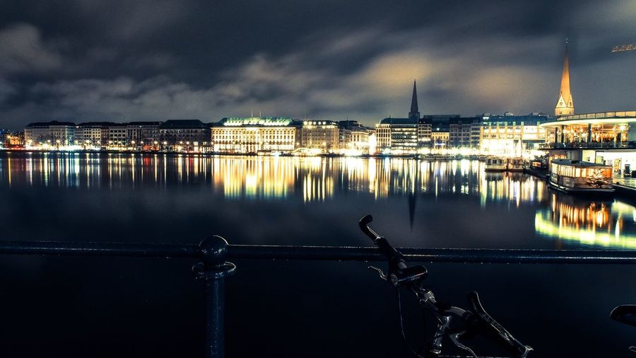 Reflection of illuminated buildings on binnenalster lake at night