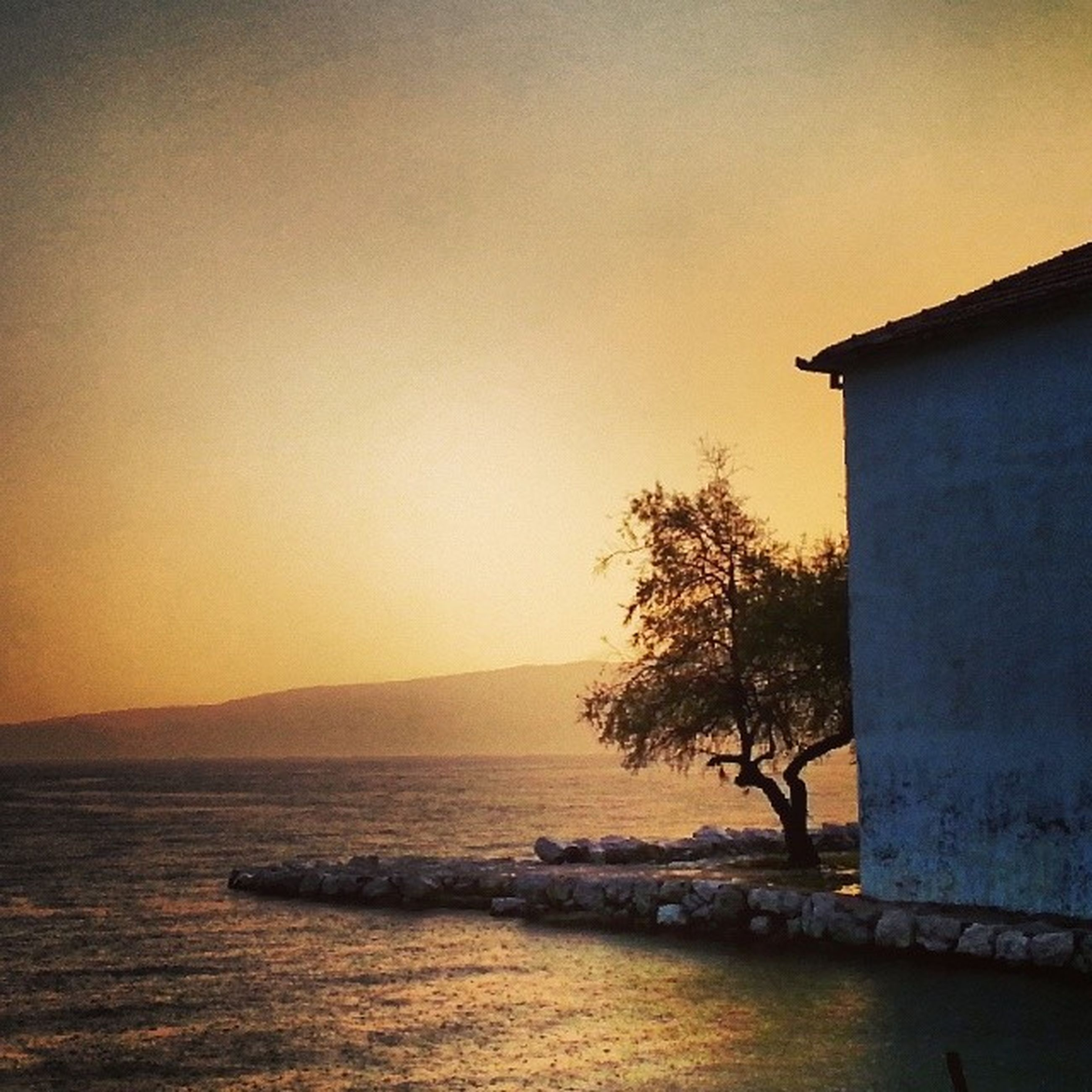 water, sea, clear sky, built structure, sunset, architecture, building exterior, copy space, tranquil scene, scenics, tranquility, waterfront, beauty in nature, horizon over water, nature, silhouette, sky, idyllic, orange color, rippled