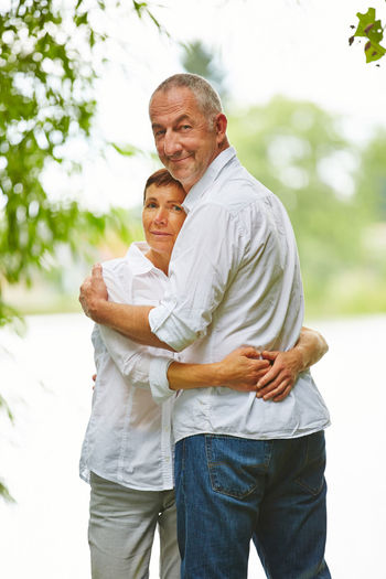 Portrait Of Couple Embracing Against Lake