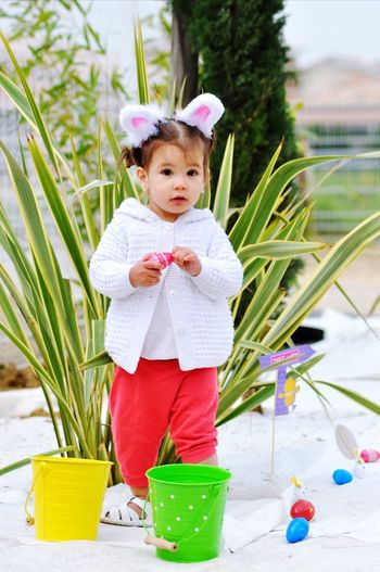 Portrait of cute girl standing by buckets and easter eggs