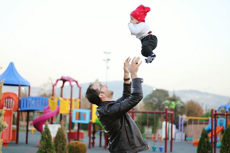 Side view of father tossing son at playground