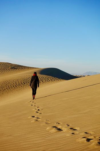 Rear View Of Woman Walking On Sand At Desert Against Blue Sky