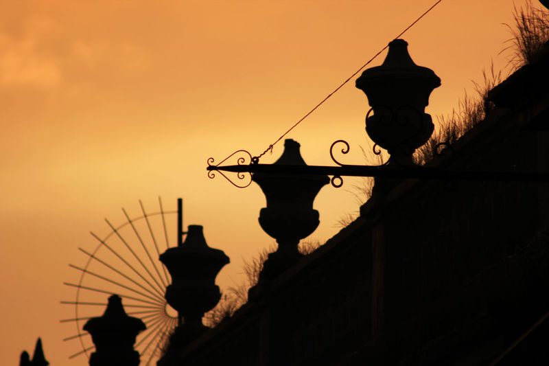 Low angle view of silhouette street light by building against sky