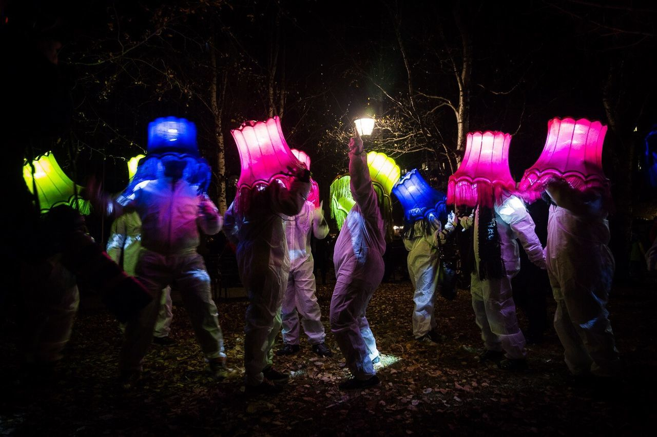 People dancing with lamp shades on head during light festival