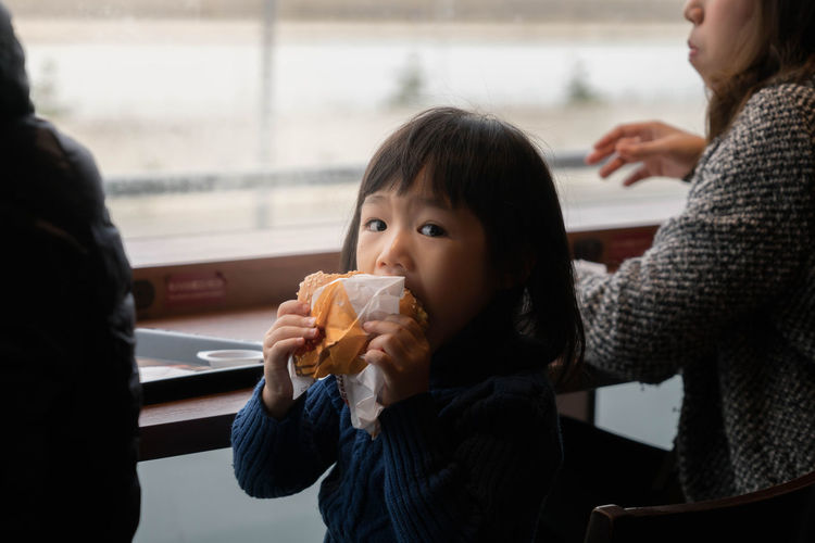Portrait Of Cute Girl Eating Fast Food With Mother