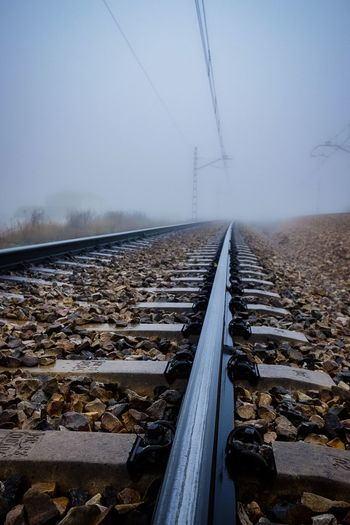 Surface level of railroad tracks against sky during winter